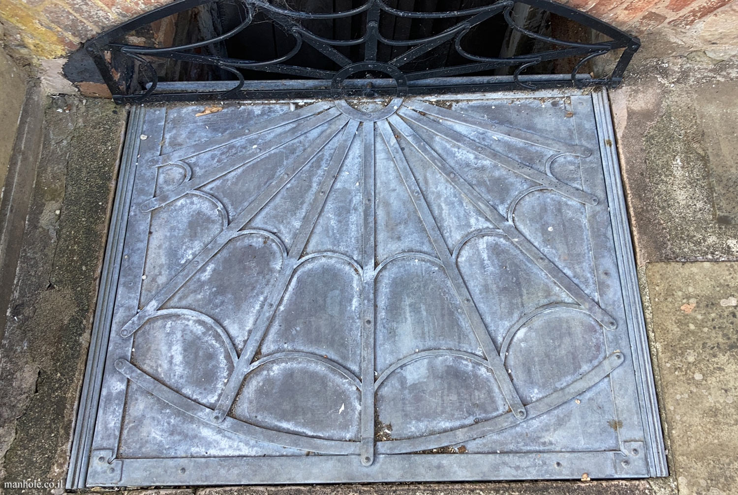 Ludlow - A lid with a background resembling a cobweb and a drain opening at the end